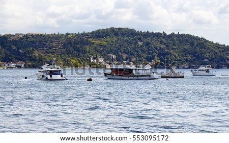 View of bay of luxury neighborhood Bebek on European side of Istanbul. Yachts, fishing boats are parked on Bosphorus. Residential buildings on Asian side are in the background. Cloudy autumn day.