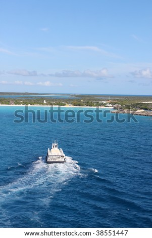 View of beach at Half Moon Cay in the Bahamas with boat approaching shore - stock photo