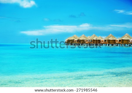 View of beautiful blue ocean water and bungalows in Baros Maldives - stock photo