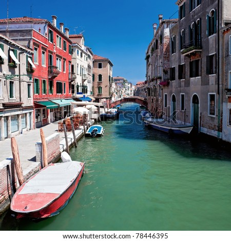 View of beautiful Venice canal with bridge and houses standing in water - stock photo