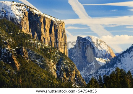 View of beautiful Yosemite valley in winter with snow covered El Capitan and Half Dome at sunset - stock photo