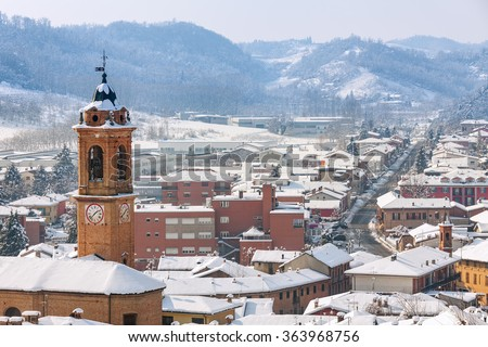 View of belfry and small town of Corneliano d'Alba covered with snow in Piedmont, Northern Italy. - stock photo