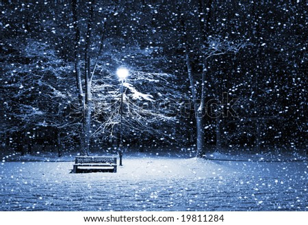 View of bench and shining lantern through snowing. Night shot. - stock photo