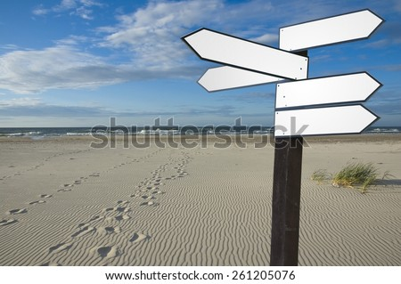 View of blank wooden multi-direction guidepost with footprints on Baltic Sea coast, Poland - stock photo