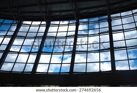 View of blue sky with clouds from glass wall of office building