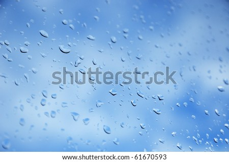 View of blue sky with clouds through window after rain