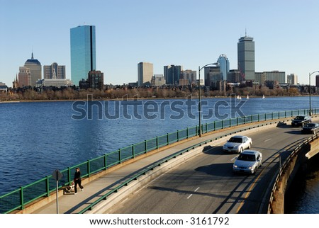 View of Boston skyline from Cambridge in late afternoon. Memorial Drive and Charles river on foreground.
