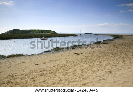 View of Brean down and moored boats in the mouth of the river Axe at Weston Super Mare Somerset - stock photo