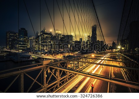 View of Brooklyn Bridge at night with car traffic - stock photo