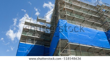View of building construction site of modern office building surrounded by scaffolding