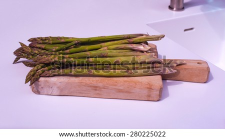 View of bunch of fresh asparagus on cutting board - stock photo