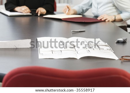 View of business women sitting with blueprints on the table. - stock photo