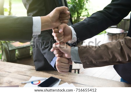 view of businessmen make sign together with notebook, laptop and wooden background.