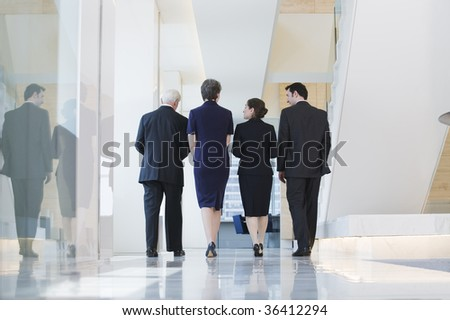 View of businesspeople walking to a meeting while discussing plans. - stock photo