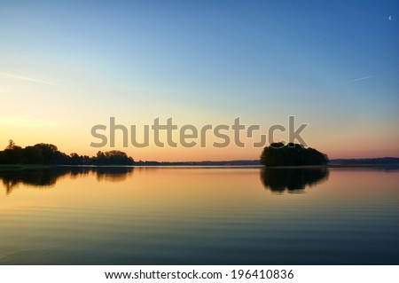 View of calm water surface just before sunrise, Mazury, Poland - stock photo