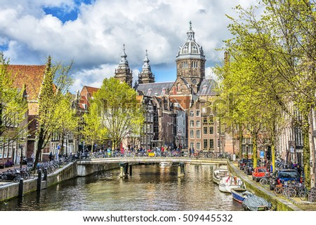 View of canal and St. Nicholas Church in Amsterdam at spring sunny day, Amsterdam, Holland, Netherlands