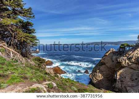 View of Carmel Bay, on a crisp spring morning, Cypress trees, blue sea & sky, & unusual rock and geological formations, as seen from the North Shore Trail, at Point Lobos State Natural Reserve. - stock photo