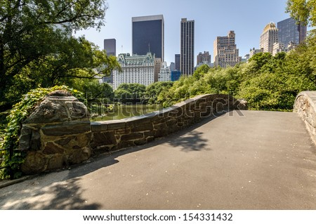View of Central Park South from Gatstow Bridge. The bridge spans The Pond on a quiet morning in Central Park springtime. - stock photo