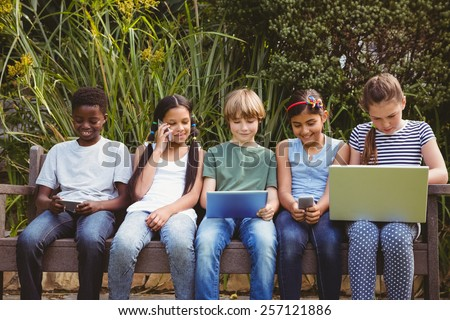 View of children using technologies at the park - stock photo