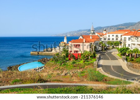 View of colorful houses in Portuguese village on coast of Atlantic Ocean, Madeira island - stock photo