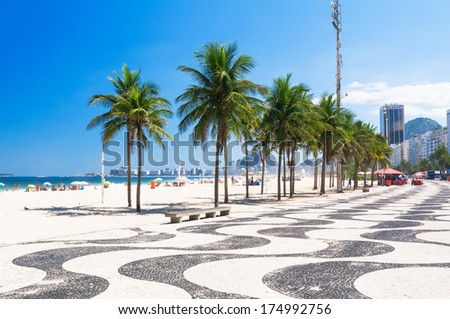 View of Copacabana beach with palms and mosaic of sidewalk in Rio de Janeiro - stock photo