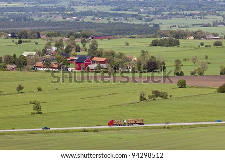view of countryside landscapes with a timber truck on the road - stock photo