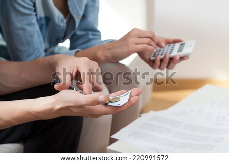 View of couple calculating money at home - stock photo