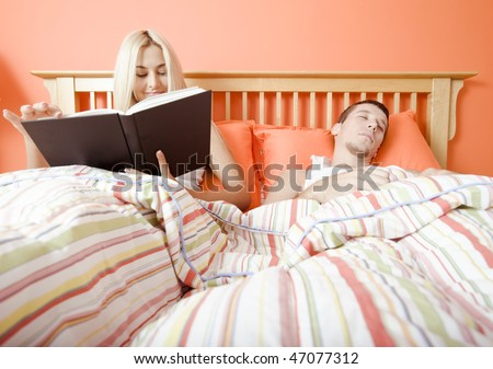 View of couple in bed, with woman reading book and man sleeping. Horizontal format. - stock photo