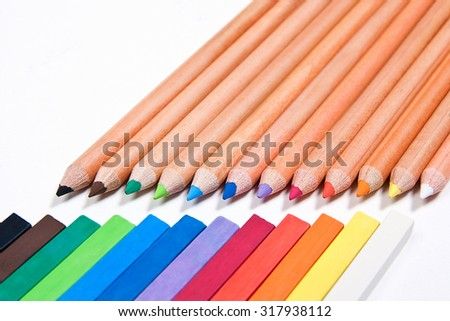View of different color pencils and chalk pastels isolated. Drawing supplies: assorted color pencils and chalk pastels, on white background. Abstract background from color pencils and chalk pastels. - stock photo