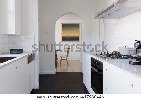 View of dining room at the end of a contemporary white galley apartment kitchen - stock photo
