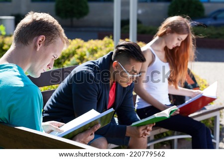 View of diverse students on a bench - stock photo