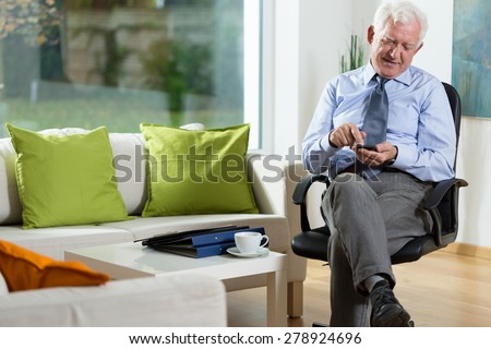 View of elderly man using mobile phone - stock photo
