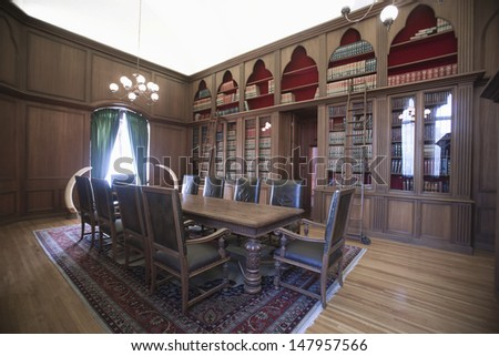View of empty table and chairs by bookshelf in an old fashioned home library - stock photo