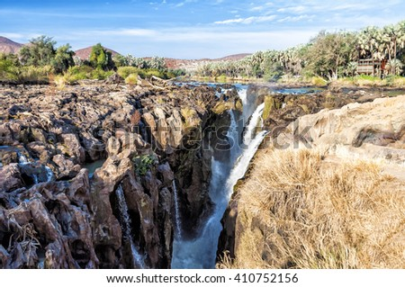 View of Epupa falls on the border of Namibia and Angola. The falls are created by the Kunene River in the Kaokoland area. Is 0.5 km wide and drops in a series of waterfalls spread over 1.5 km. - stock photo