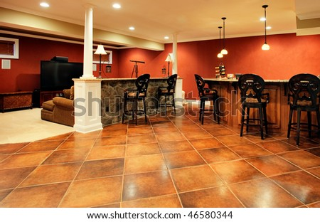 View of family room with bar, home theater area, and parquet floor. Horizontal format. - stock photo