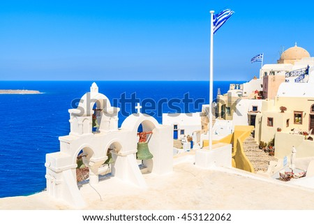 View of famous Oia village with typical church tower and Greek flag, Santorini island, Greece