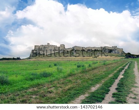 View of field road to famous Spis Castle (Spissky hrad) ruin in summer. Spis Castle is popular symbol of Spis region, Eastern Slovakia. This castle is included in the UNESCO World Heritage List.