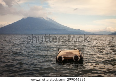 View of floating wooden dock and volcano, sunset over Lake Atitlan and Jaibalito in Guatemala  - stock photo