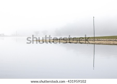 View of foggy landscape at Amazon river in Brazil with a bird standing on a long wooden stick. The misty scene evokes sensations of calmness, peace and tranquility - stock photo