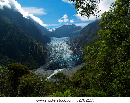 View of Fox glacier through the tropical forest in new zealand - stock photo