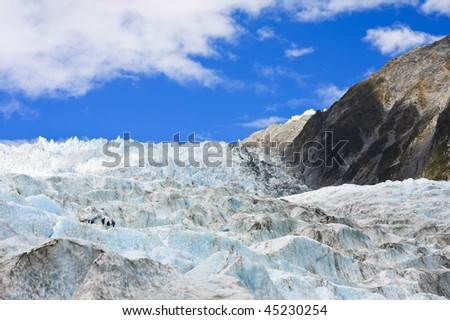 View of Franz Joseph Glacier with Hikers in New Zealand, South Island. - stock photo
