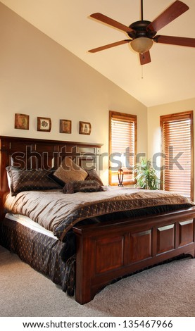 view of furnished bedroom with vaulted ceiling and ceiling fan - stock photo