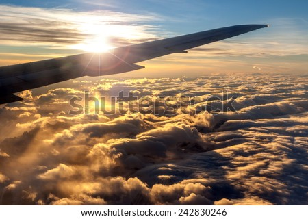 View of golden sunrise outside airplane window with deliberate lens flare over plane wing silhouette for effect. A sea of clouds over the Rocky Mountains underneath the plane glisten off the sunlight. - stock photo