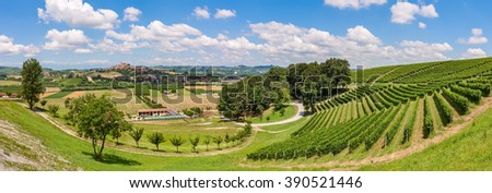 View of green fields and vineyards under blue sky with white clouds in Piedmont, Northern Italy (panorama). - stock photo