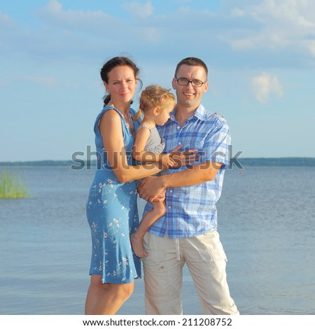View of happy young family having fun on the beach. happy young family in a blue dress have fun at vacations on beautiful beach