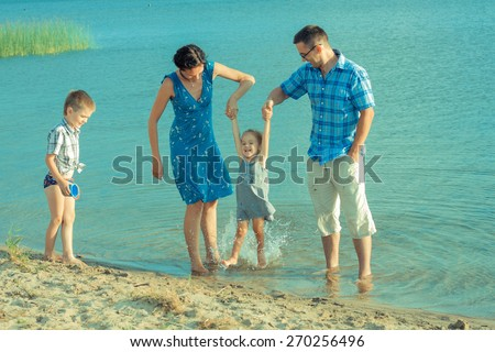 View of happy young family having fun on the beach. happy young family in a blue dress have fun at vacations on beautiful beach - stock photo
