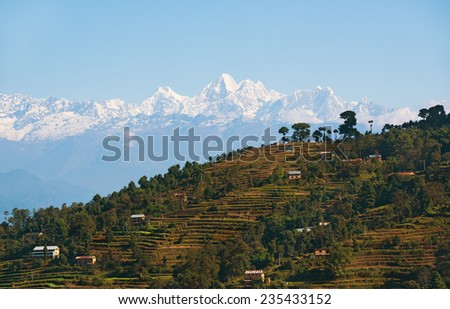 View of Himalayan village with mountain backdrop - stock photo