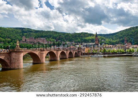 View of Historic Old Bridge Crossing Neckar River to Old Town Heidelberg, Baden-Wurttemberg, Germany on River Bank Below Lush Green Foothills - stock photo
