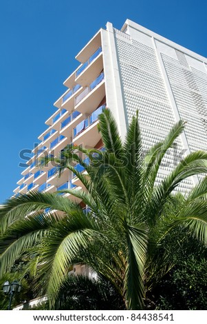 View of hotel and palm tree against blue sky. - stock photo