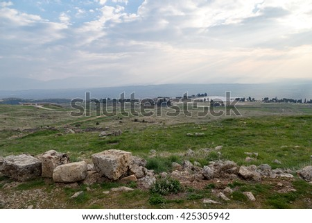View of Hyerapolis Ancient City with stone ruins on cloudy sky background.
